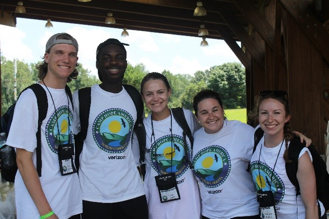 Group of smiling people in camp t-shirts