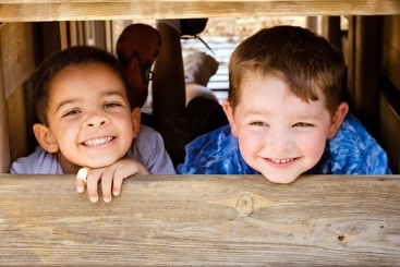 Two young children grinning through gap in boards