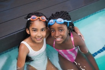 Two girls smiling in swimming pool