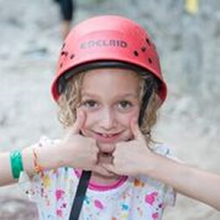 Girl in climber's helmet giving thumbs-up